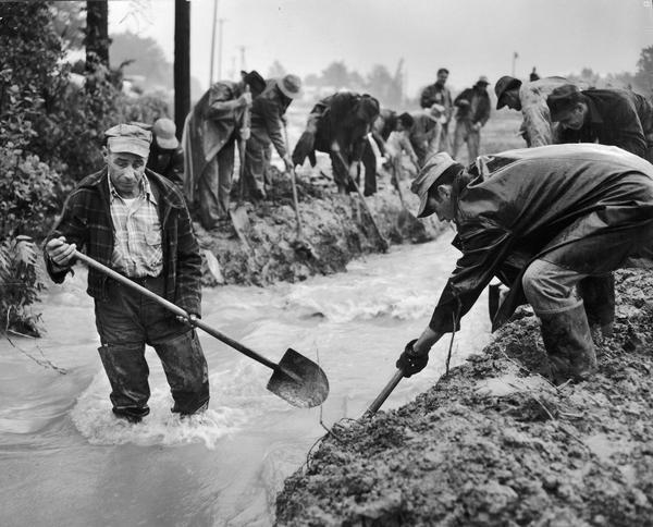 Men with shovels during the flood at Villa Louis.