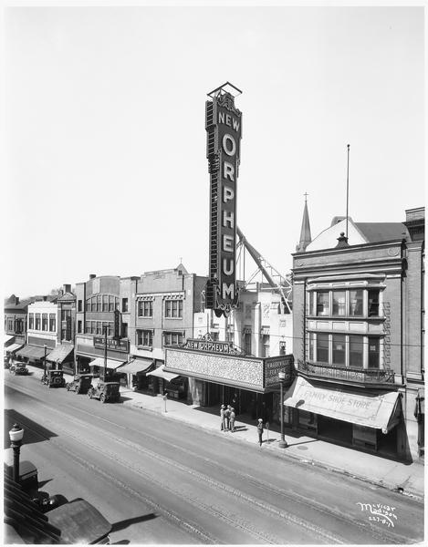 "Elevated view of buildings in the 200 block of State Street, with the Orpheum Theatre as a focal point. The theatre marquee reads ""New Orpheum."" Next door to the theatre on the right is The Family Shoe Store. On the left is Brown & Barels, Speth's Clothes, the Cardinal Pharmacy, and a floral company."