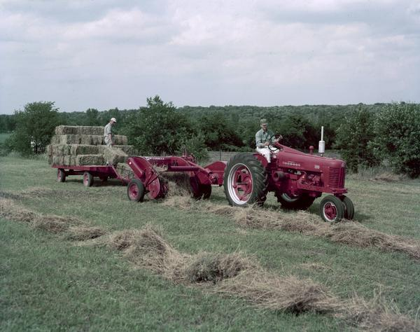 Color photograph of two men operating a Farmall 300 tractor and a McCormick baler in a field.