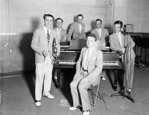 "Anthony ""Tony"" Salerno's Gypsy Melodians at WIBA radio station standing around a piano. Tony is holding his violin, the other Melodians are standing around the piano, and Otto Heinz is sitting in front. Ben Ehr, sax and clarinet; Earl Barnes, trombone; Erwin Krueger, drums; and William Kraft, cornet."
