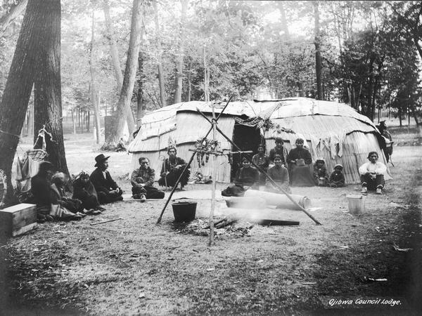 Ojibwa chief's lodge from Lac Courte Orielles Reservation set up at the 1906 Wisconsin State Fair. Note both reed and bark coverings on the lodge. A number of Indians - men, women and several children - sit in front of the lodge, and there is a fire pit in the foreground.