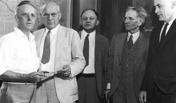 Neils Ruud, 824 E. Dayton Street, receiving the first unemployment compensation check issued in Wisconsin from Voyta Wrabetz, chairman of the state industrial commission. Also shown is Edwin Witte, university economist and author of the national social security act, Professor John Commons, university economist, and Ruud's employer H.H. Brockhausen.