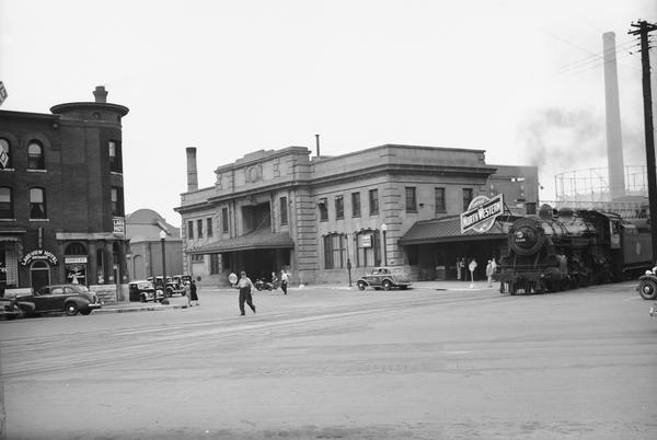 Exterior view of the Chicago & Northwestern railroad station, 219 S. Blair St., along with the Lake View Hotel, 524 E. Wilson St, in Madison. A man holding a stop sign is in the road between the buildings.