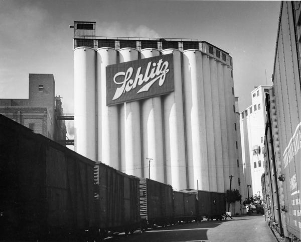 Grain elevator with large Schlitz sign. There are railroad cars on a railroad track in the foreground.