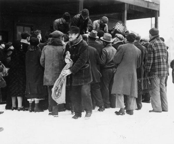 People receiving fish at a relief station in the wintertime.