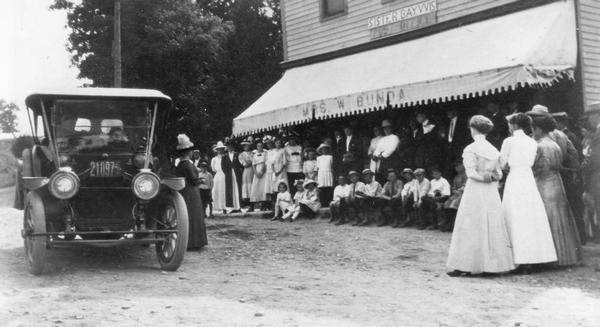 Suffragist Mrs. Katherine McCullough speaking to a gathering in front of the store and post office run by Mrs. W. Bunda in Sister Bay.