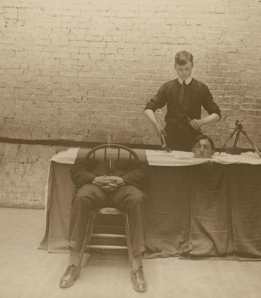 William C. Klatt, member of the Menomonie High School class of 1905, depicted as a physician operating on a disembodied head. Darkroom manipulation was used to create the illusion of the separation of the patient's head from his body.