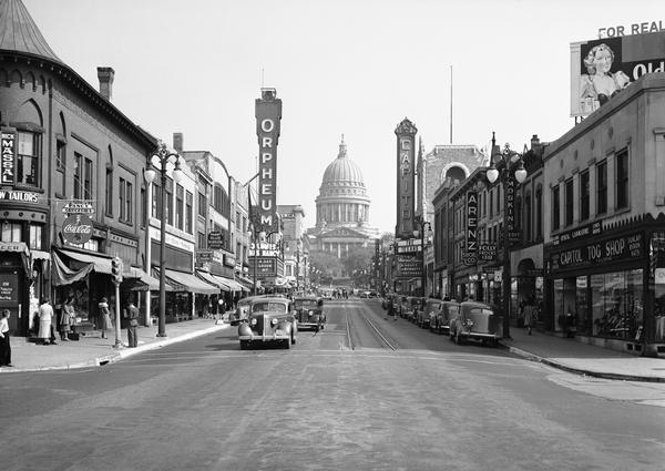 A view from the 200 block of State Street looking toward the Wisconsin State Capitol. This urban scene includes marquees for the Orpheum Theater and the Capitol Theatre, storefronts, traffic, and pedestrians.