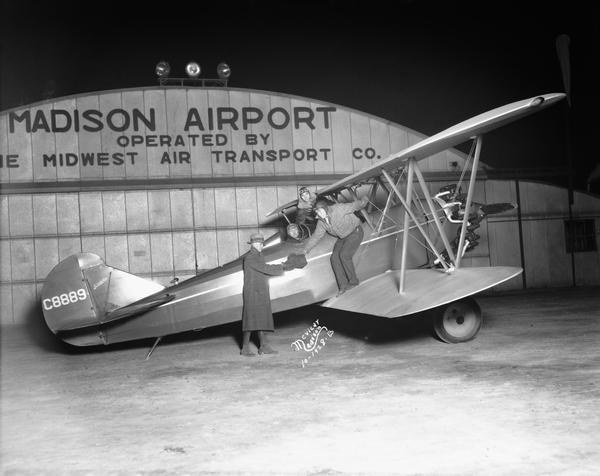 "Travelair plane returning to the Madison Airport from a Wisconsin v. Purdue football game. Here photographer Aldro Wasley is handing photographs of the game to a ""Capital Times"" representative. Pilot Orland G. Corben and another passenger are in the background."