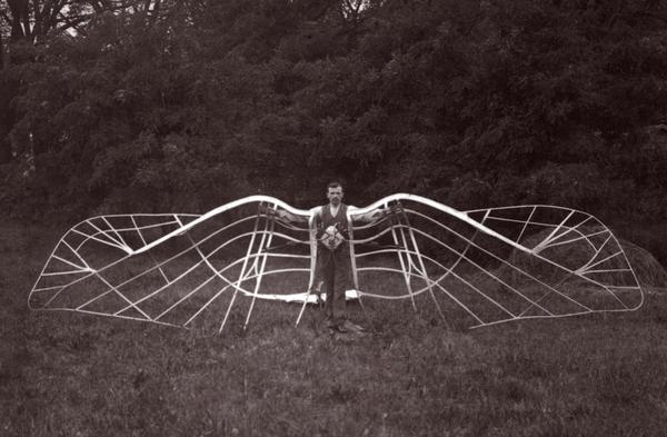 An unidentified man demonstrates his unsuccessful bird wing-like mechanism, which was part of an experiment in aviation.