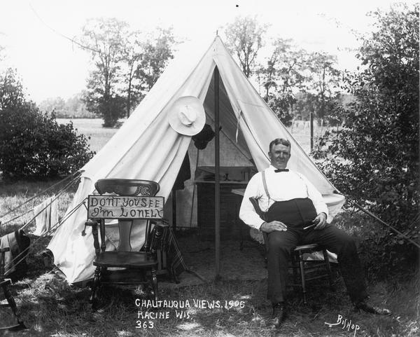 "A man in bow tie and suspenders sits in front of a small tent. Next to him is a rocking chair with a sign on it that says ""Don't you see I'm Lonely."" Written onto the negative is ""Chautauqua Views. 1906 Racine Wis, 363."""