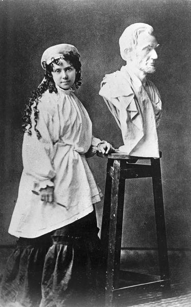 Vinnie Ream posing in her studio in Washington, beside her bust of Lincoln which had been brought from the White House after the assassination.