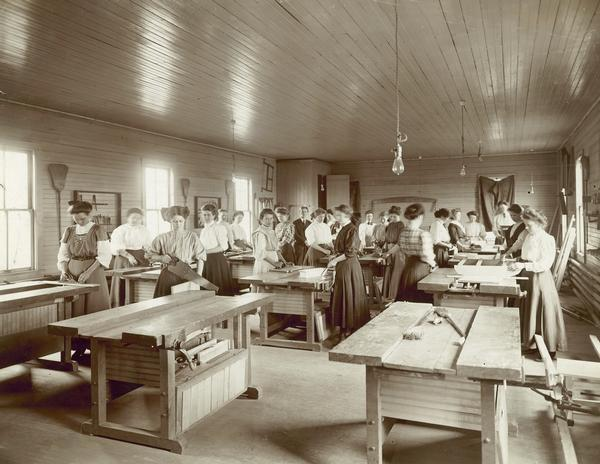 Women working with tools, including a saw, in the University of Wisconsin Agricultural Extension women's carpentry class.