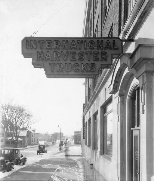 "Cars and houses along a snowy street as seen from under a neon ""International Harvester Trucks"" sign."