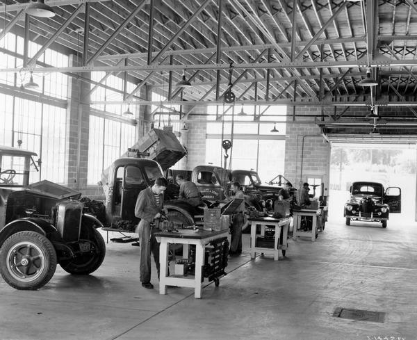 "Mechanics working inside the service center of an International Harvester dealership. The door of one of the trucks is painted ""McCormick-Deering Store."""
