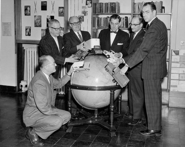 Six International truck executives posed with model trucks on large globe at International Harvester's Fort Wayne Works.