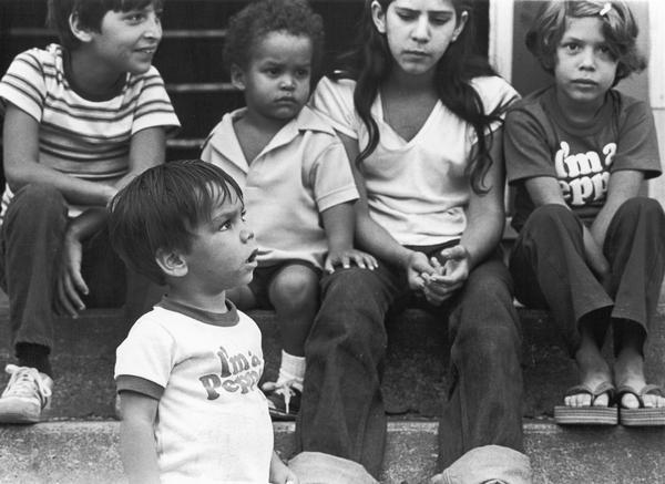 "Children sitting on steps. Two of them are wearing ""I'm A Pepper"" t-shirts. Photographs made on July 4, 1980, by Archibald of Cuban refugees who had arrived as a result of the Port of Mariel exodus, and were housed at Camp McCoy, Wis.; including images of the camp life of Cuban men, women, and children."