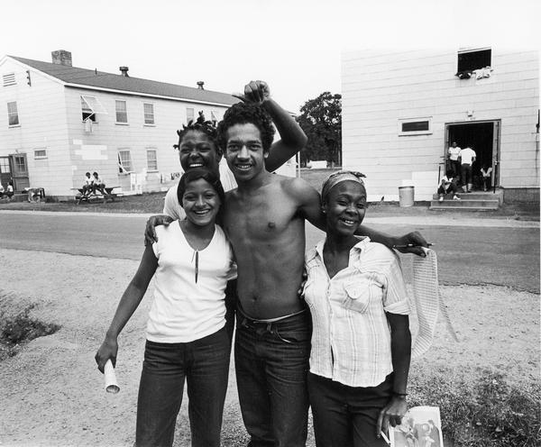 Four smiling young Cubans with petitions for camp nomination elections. Photographs made on July 4, 1980, by Archibald of Cuban refugees who had arrived as a result of the Port of Mariel exodus, and were housed at Camp McCoy, Wis.; including images of the camp life of Cuban men, women, and children.