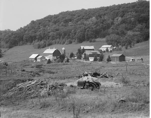 Farm buildings in the Coulee country, with old tractor in foreground.
