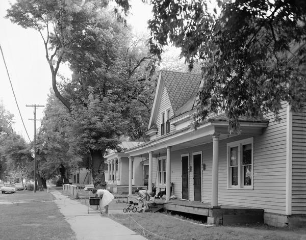 Old houses in a residential neighborhood with women and children at play.