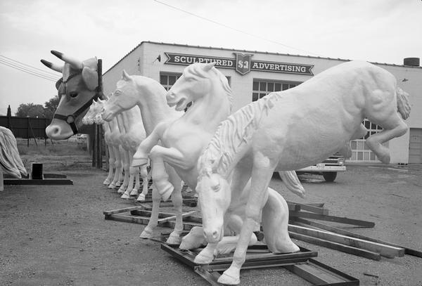 A row of sculptured horses and a cow's head at the Creative Display Company, currently known as the FAST Corporation.
