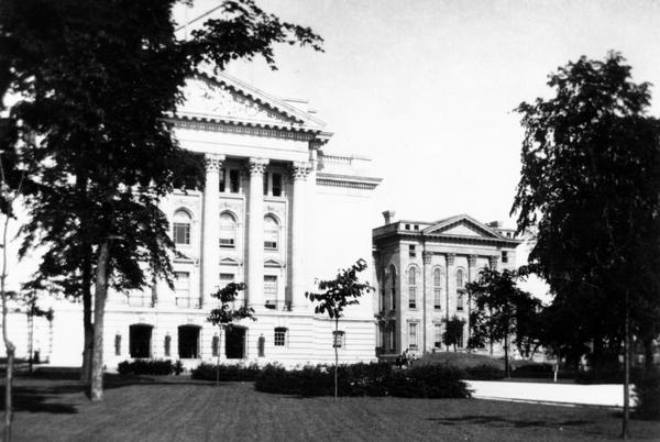The fourth Wisconsin State Capitol on the left, with the North Wing of the old Capitol still standing at right.  The North Wing was not damaged by the fire of 1904 and it continued to be used until 1913.