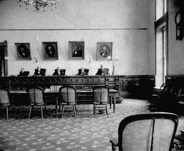 Interior view of the Supreme Court room in the third Wisconsin State Capitol, with Chief Justice William Penn Lyon seated in the center, and Justices J.B. Winslow, John B. Cassoday, Harlow S. Orton, and Silas U. Pinney around him. This photograph shows the impressive two-story  courtroom in the North Wing that was occupied by the Supreme Court after the expansion of 1883.