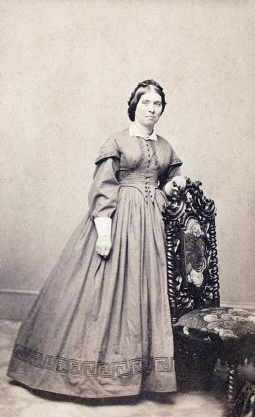 Formal studio photograph of a woman standing next to a chair.