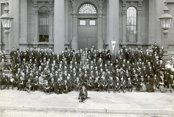 A group of Civil War veterans and their families pose in front of the Milwaukee armory building at the reunion of The Iron Brigade.