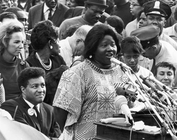 Johnnie Tillmon addressing a Mother's Day March on Washington, ca. 1968 or 1969. George Wiley sits directly behind her, on the left. Ethel Kennedy looks on.
