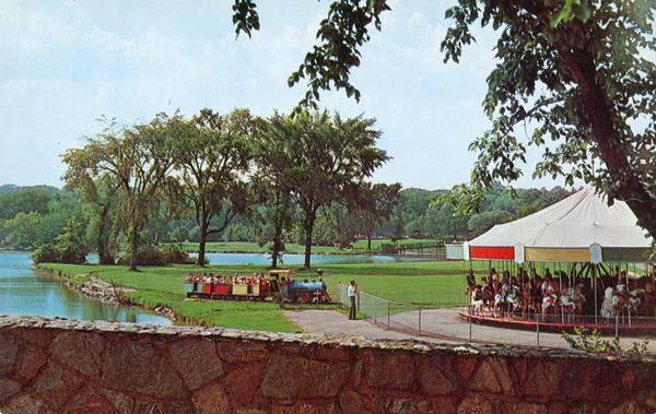 View from a stone bridge towards Vilas Park, with children riding the carousel (merry-go-round) and a kiddie train adjacent to the lagoon.