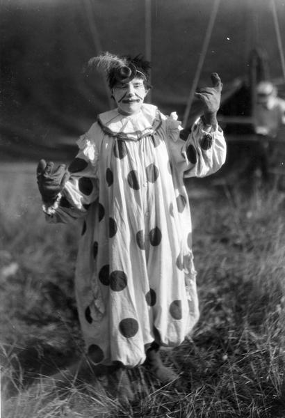 A clown wearing a small hat with a feather, a polka-dotted suit, and large gloves, stands near a tent.