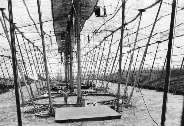 A view of the inside of a circus tent being readied for a performance.