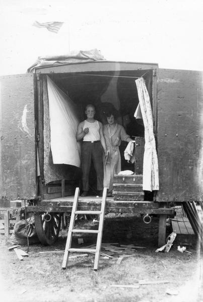 A man and a woman, in the process of getting dressed for a circus performance, pose informally in the back of a circus wagon.