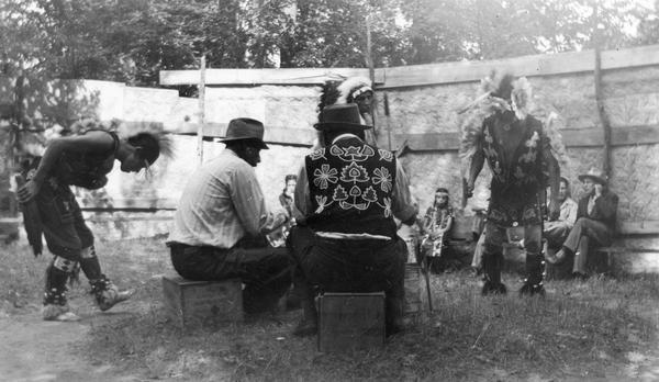 A Menominee ceremonial dance. The dancers are wearing Native American ceremonial dress. Although Roman Catholic missions had banned many Native American ceremonies and dances, rules were gradually relaxed as dances became tourist attractions rather than forms of religious expression. Note the drum circle worn in the grass. This image is part of an exhibit about Native Americans prepared by Paul Vanderbilt, the Wisconsin Historical Society's first curator of photography.
