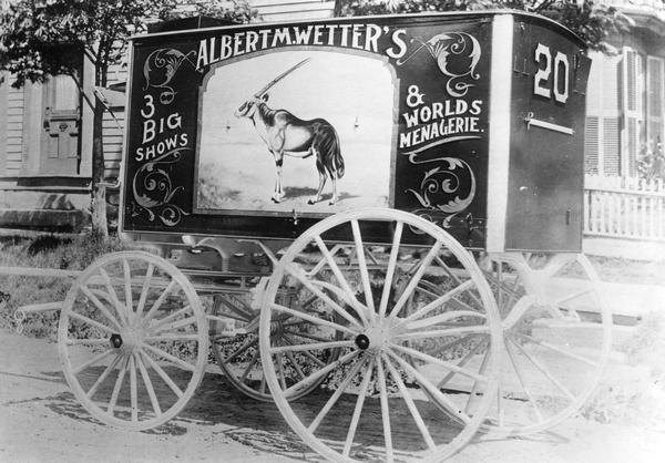 Wagon number 20, advertising Albert M. Wetter's 3 Big Shows & World's Menagerie, is parked at a curb next to a private residence.