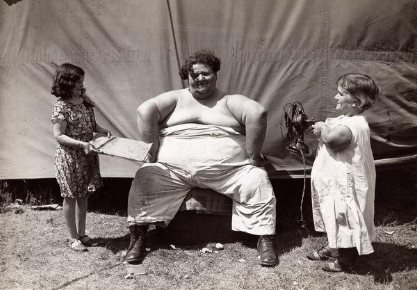 A circus sideshow performer sits outside a tent talking with a young girl and what is most likely a woman who is a dwarf.