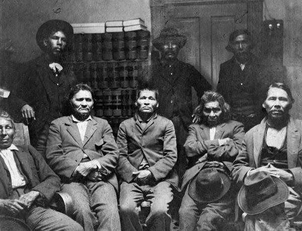 A group of locally important Potawatomi Indians, apparently photographed in a government or law office at Escanaba, Michigan.  Left to right standing are Fred Jones Wanka, Joe Negahnee, and Wis-Ki-Ge-Amatyuk, also known as John Buckshot (Prairie Band Potawatomi, Kansas, principle pipe carrier and ritual leader). Seated left to right are Joseph Waumegesake (or Wampum, a descendent of the older chief Wampum, born in Manitowoc), Abraham Michicot (or Mishegand, who was born at Mink River in Door County), David Nsa-waw-quet (or Crutch, reportedly the best hunter and trapper in Michigan), Ben Ah-quee-wee (Dr. Ben), and William Keeshik of the Manitowoc band.