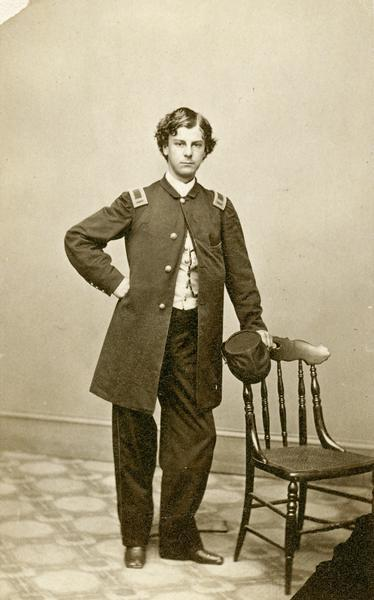 Studio portrait of young Lieutenant Colonel Arthur MacArthur Jr., F & S, 24th Wisconsin Infantry, posing in a Civil War uniform next to a chair.