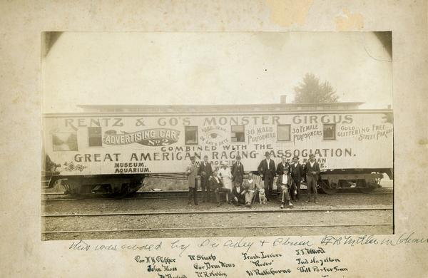 A group of personnel with the Rentz & Co.'s Monster Circus combined with the Great American Racing Association, pose for a photograph by the side of the train car advertising the show.