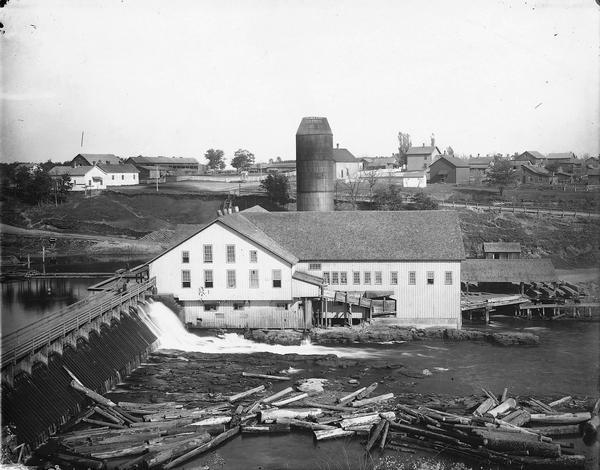 Knapp-Stout and Company Sawmill on the Red Cedar River, with dam and logs in the foreground.