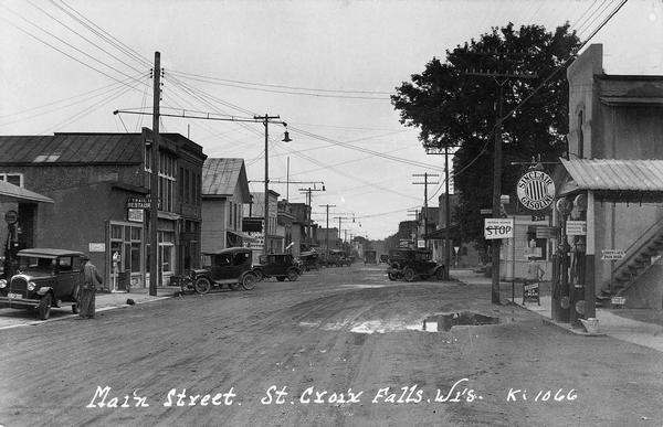 Main Street, with two competing curb-side gas stations across the street from each other. Cars are parked along both sides of the muddy street.  Such curb-side service stations were typical of the early days of automobiles.  Perhaps the large mud puddle in front of the Sinclair gas pumps has given the advantage this time to the station on the left.