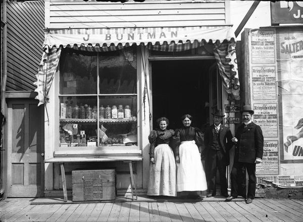 Two men and two women are posing in front of the J. Buntman store. Jars of penny candy, cans of spices, and American flags are some of the items displayed in the window. Signs in German reflect the ethnicity of the population.