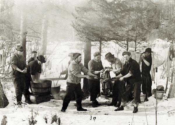 The men of Rice Lake Lumbering Camp #6 do their laundry on a Sunday.