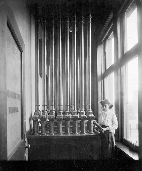 A worker stands next to a pneumatic tube communication system used at the Milwaukee Electric, Railway, and Light Company.