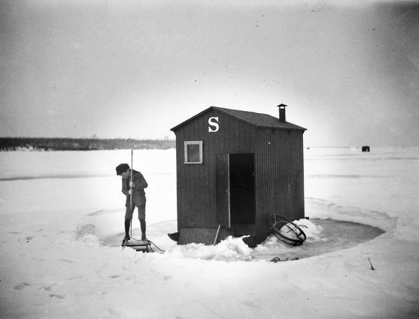 A boy dressed in knickers clears the ice in preparation to fish next to his family's ice shanty.