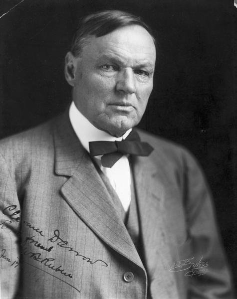 Quarter-length portrait of Clarence Darrow, signed by Darrow and embossed by photographer Mabel Sykes.