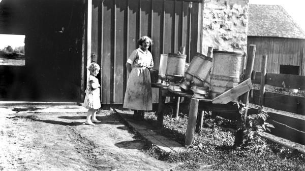 Elna and little Shirley Krueger with milk cans on the Krueger farm.