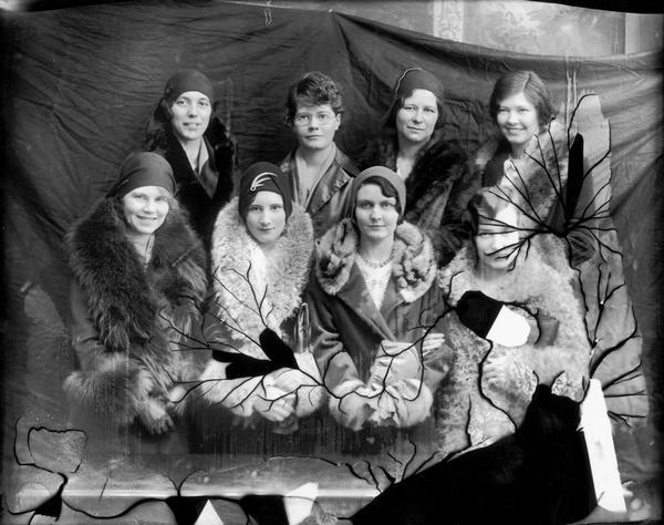 Studio portrait of women who are taking flying lessons.  Several of the women are dressed in furs.