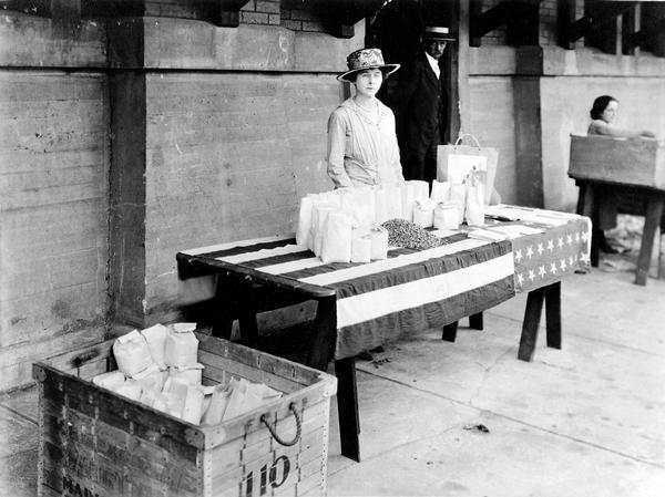 A member of the Dane County Council of Defense Food Board Women's Committee sells dried corn at the farmer's market. Women's organizations sold wheat substitutes to insure compliance with food conservation measures.  Over 3000 lbs. were sold in 1918. In 1917, the Catholic Women's Club installed a food drier at the market, which they operated as a patriot's work.